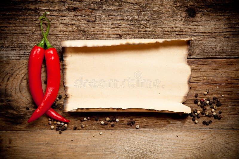 Chili Peppers d'un rouge ardent avec la vieille feuille de papier photo libre de droits