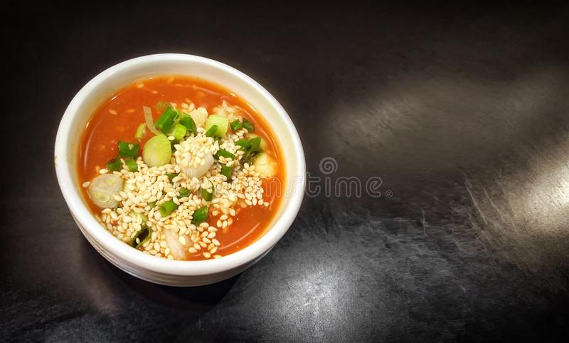 Chili Sauce Mixed con ajo picadito, la cebolla verde y el sésamo blanco en un plato en un fondo oscuro fotos de archivo libres de regalías