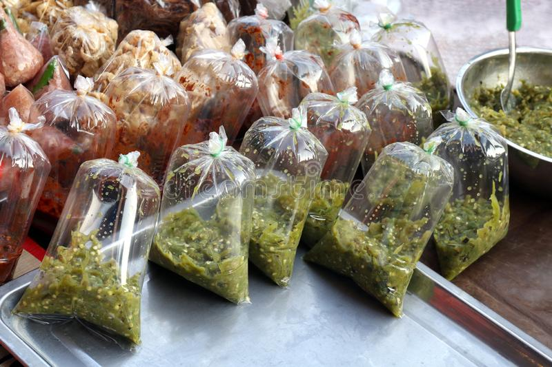 Chili sauce, chili paste, pepper sauce chili in plastic clear bag at thai street food market, vegetable chili thai tasty food stock images