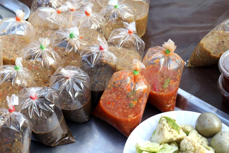 Chili sauce, chili paste, pepper sauce chili in plastic clear bag at thai street food market, vegetable chili thai tasty food stock photos