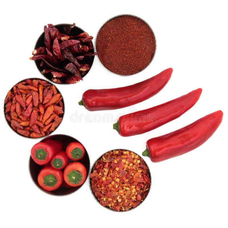 Chili Spice Selection. Chili spice collection of powder, dried and flakes in bowls with loose fresh chilies over white background stock image