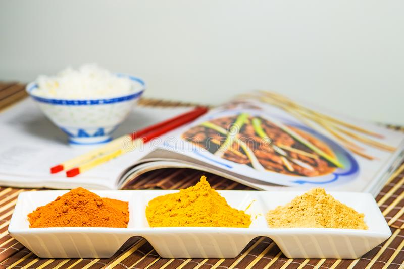 Chili, turmeric, ginger powder in bowls with cookbook royalty free stock photos
