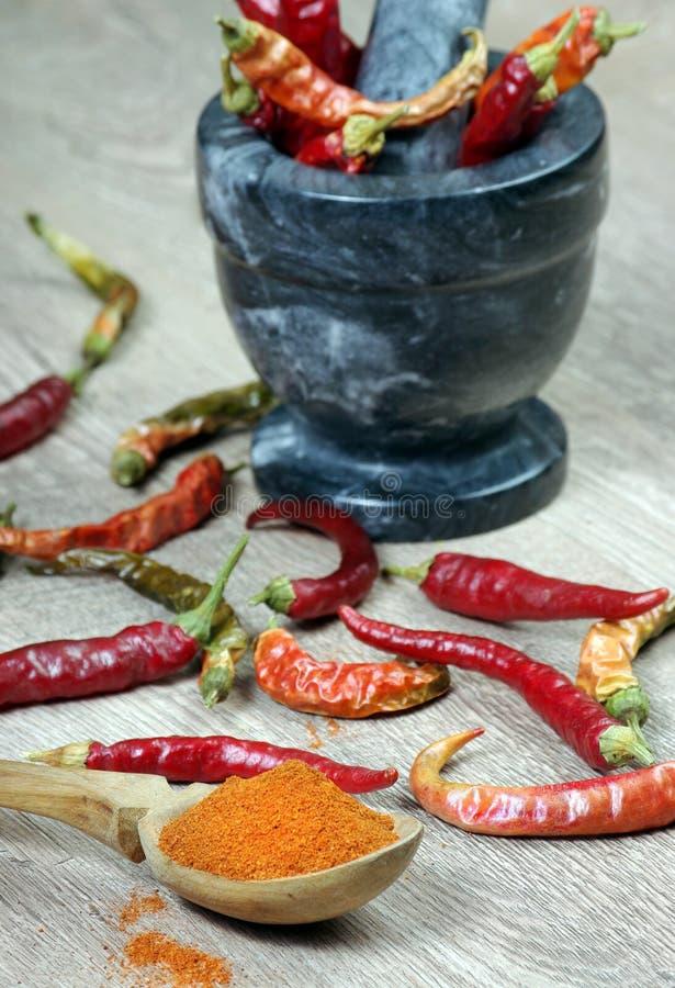Chilipeppar i en mortel hugga av peppar för röd chili i en mortel Top beskådar arkivfoto