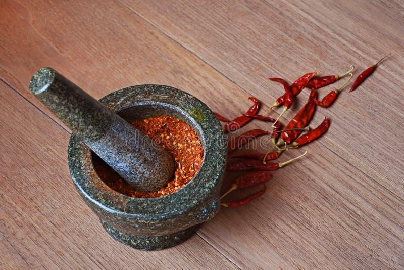 Chilipeppar i stenmortel och torkade chili på träbackg arkivbild