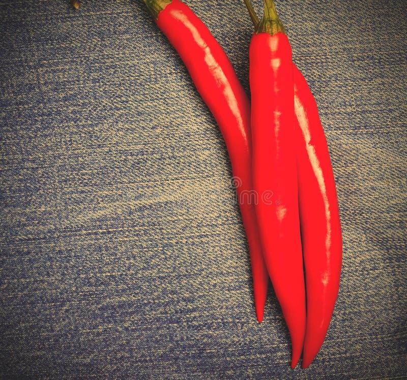Chilipeppar på jeans arkivbilder