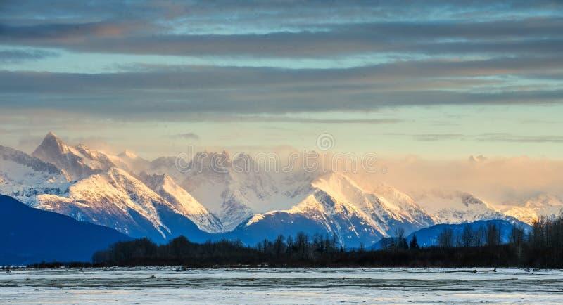 Chilkat flod och berg i snö på en soluppgång arkivbild