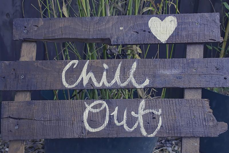 Chill out sign. Chill out words hand painted on boards.Positive garden decoration element.Cool sign.Insprational quotee,text.Uk lifestyle.Relaxing athmosphere stock images