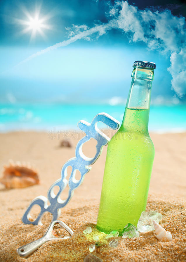 Chilled beer on the beach. Beautiful composition of chilled beer, beach, bottle opener and amazing sky. Look at my portfolio for more cocktails stock image