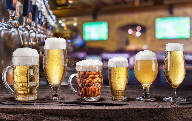 Chilled mugs and glasses of beer on the old wooden table. Pub interior and bar counter with beer taps at the background stock photo