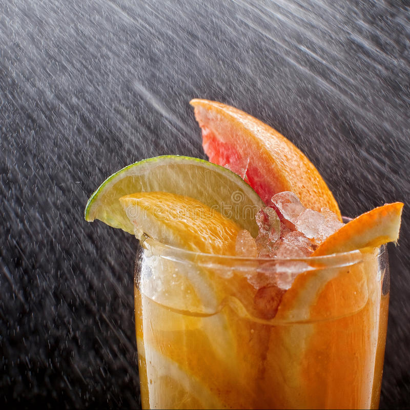 Chilled soft drinks with ice, citrus fruits and berries, black background, selective focus drop royalty free stock images