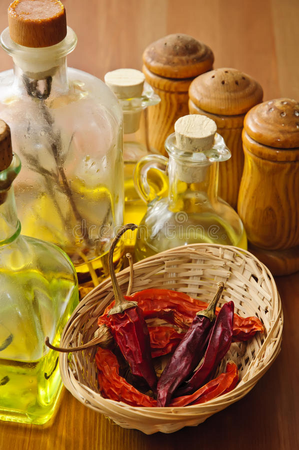 Chilli, olive oil and condiments. Dried chilli with olive oil and condiments on a wooden background royalty free stock photo