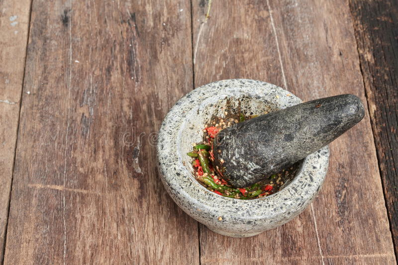 Chilli pepper in stone mortar on the wooden table royalty free stock image
