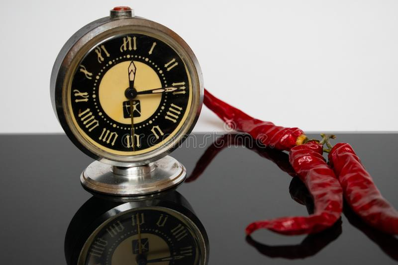 Chilli peppers  and vintage watch on a reflective surface. Still life time and taste stock image