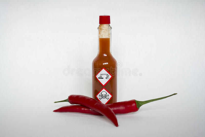 Chilli sauce with chemical hazard warning labels stock images