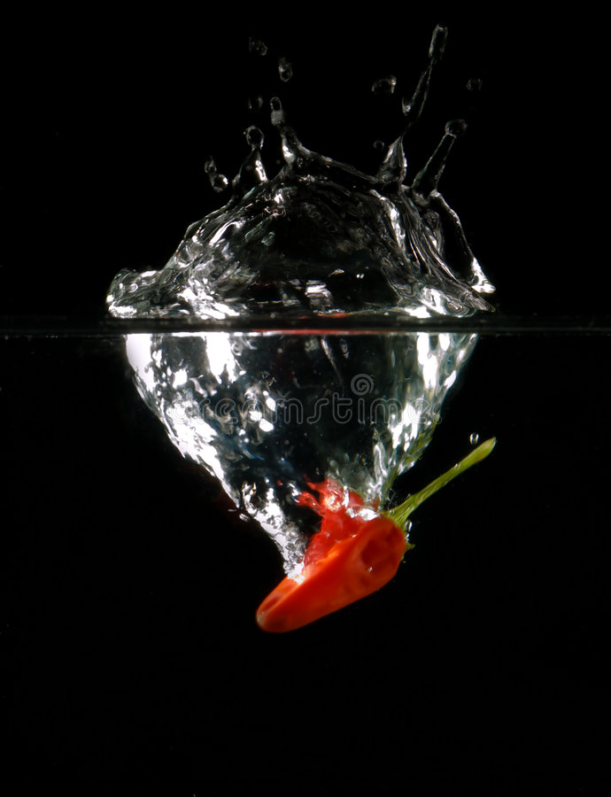 Chilli splash. Chilli in the water with air bubbles royalty free stock images