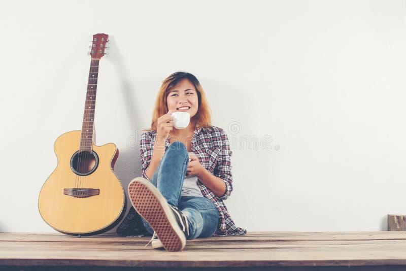 ` Chillin кофе молодой женщины битника выпивая с sittin гитары стоковая фотография rf