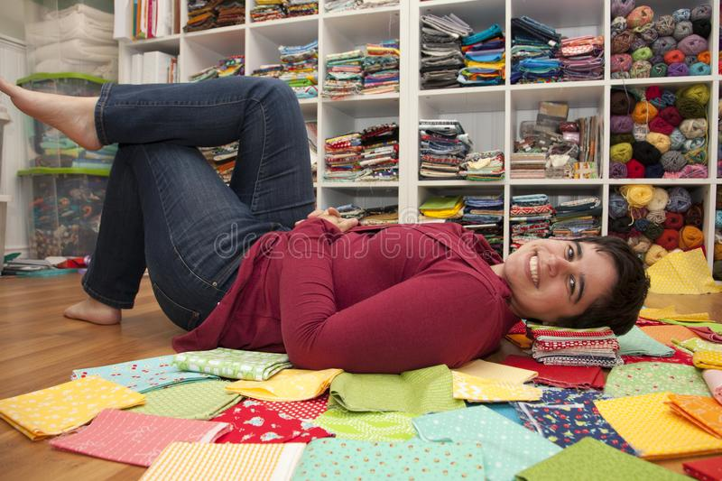 Chillin` in the craft room. Woman takes a break from crafting and lays amongst all her fabric stock image
