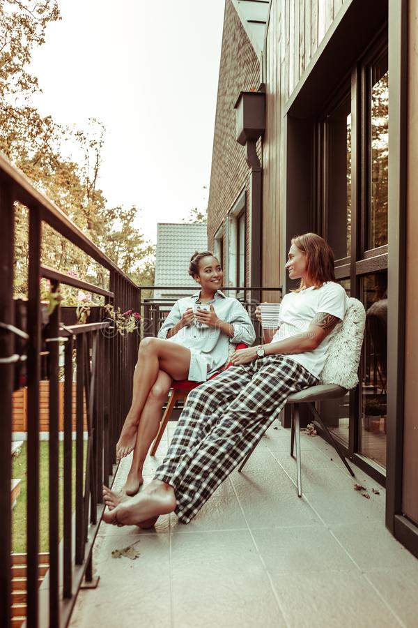 Beaming good-looking young people having pleasant conversation in the morning. Chilling on the armchairs. Beaming good-looking young people having pleasant stock image