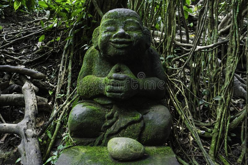 Chilling buddha statue in green, Bali monkey forest. Lush green forest stock photo