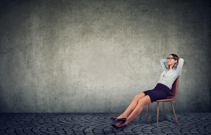 Chilling businesswoman sitting on chair stock image