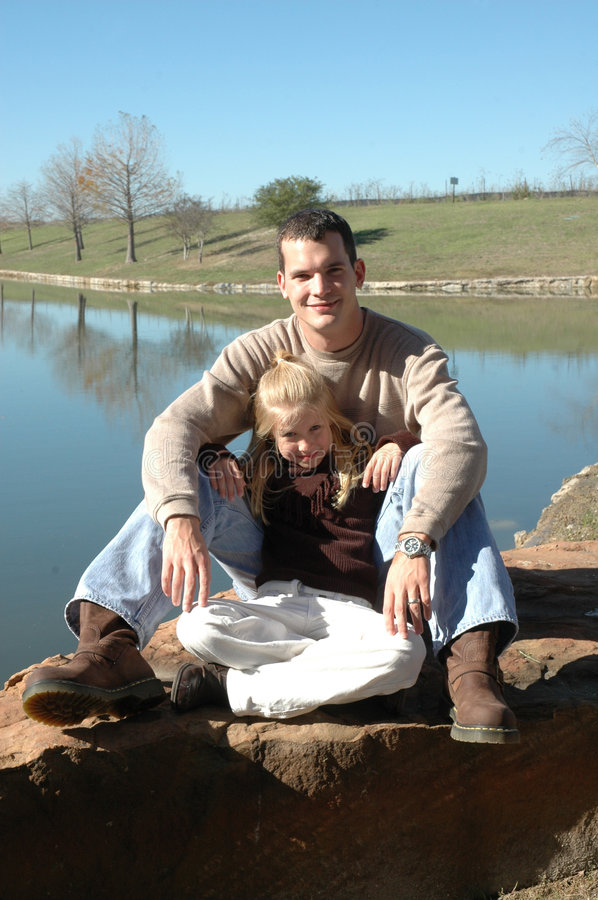 Chilling with Dad. A little girl leans back on her dad as they sit on a rock in front of a pond at the park. Father and daughter time royalty free stock images