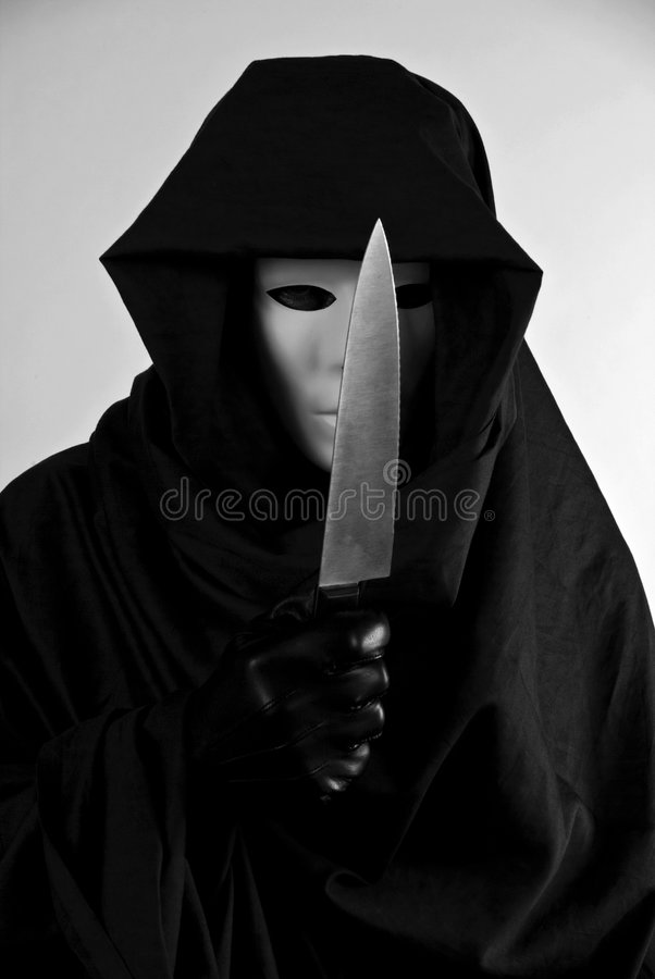 Chilling Masquerade. A person in a mask and a hooded cloak holding a butcher knife in a chilling, threatening manor royalty free stock photo