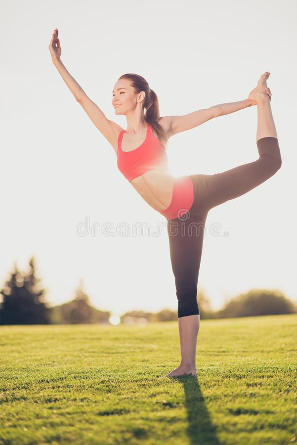 Chilling on the sun and fresh air. Wellbeing, wellness, vitality. Freedom lifestyle. Young sporty woman is practicing yoga in the park outdoors in fashionable stock image
