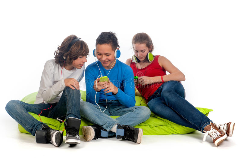 Chilling teenagers. Three teenagers, chilling on a green beanbag, lisiting to some music and using there mobile phones royalty free stock images