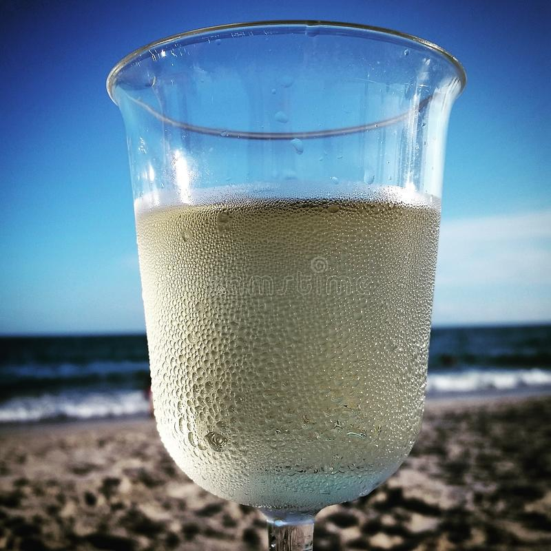 Chilling. White wine on the beach at sundown stock photos