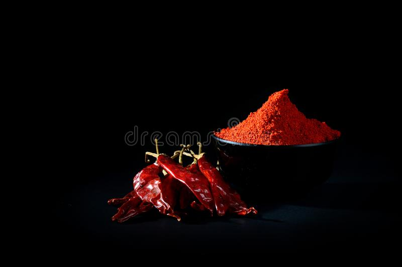 Chilly powder with red chilly in white plate. Chilly powder in black bowl with red chilly, dried chillies on black background stock photos
