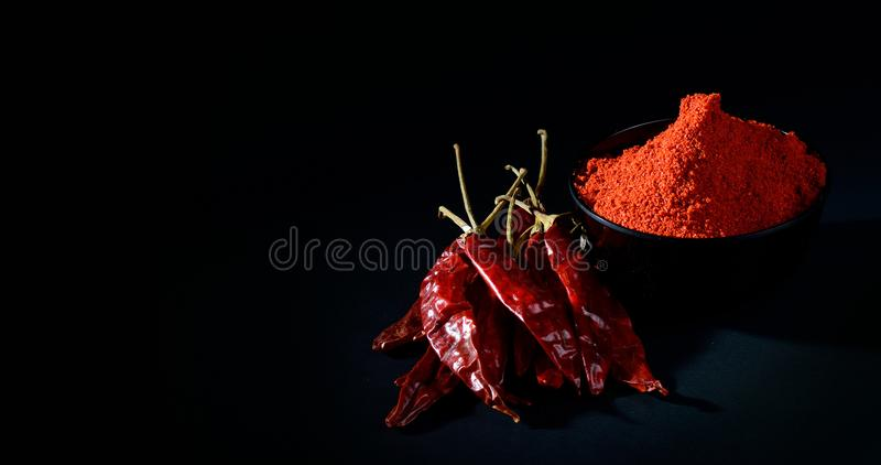 Chilly powder with red chilly in white plate. Chilly powder in black bowl with red chilly, dried chillies on black background royalty free stock photos