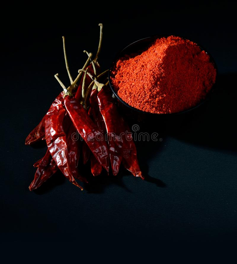 Chilly powder with red chilly in white plate. Chilly powder in black bowl with red chilly, dried chillies on black background royalty free stock images