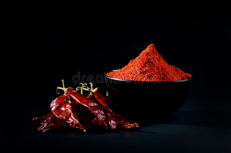 Chilly powder with red chilly in white plate. Chilly powder in black bowl with red chilly, dried chillies on black background stock photography