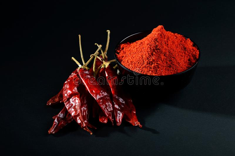 Chilly powder with red chilly in white plate. Chilly powder in black bowl with red chilly, dried chillies on black background stock images