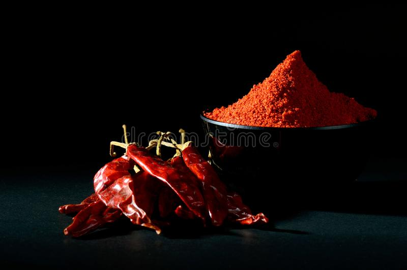 Chilly powder with red chilly in white plate. Chilly powder in black bowl with red chilly, dried chillies on black background royalty free stock photo