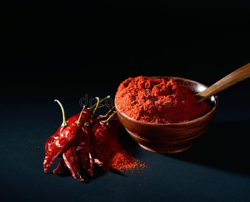 Chilly powder with red chilly in white plate. Chilly powder in wooden bowl with red chilly, dried chillies on black background royalty free stock photography