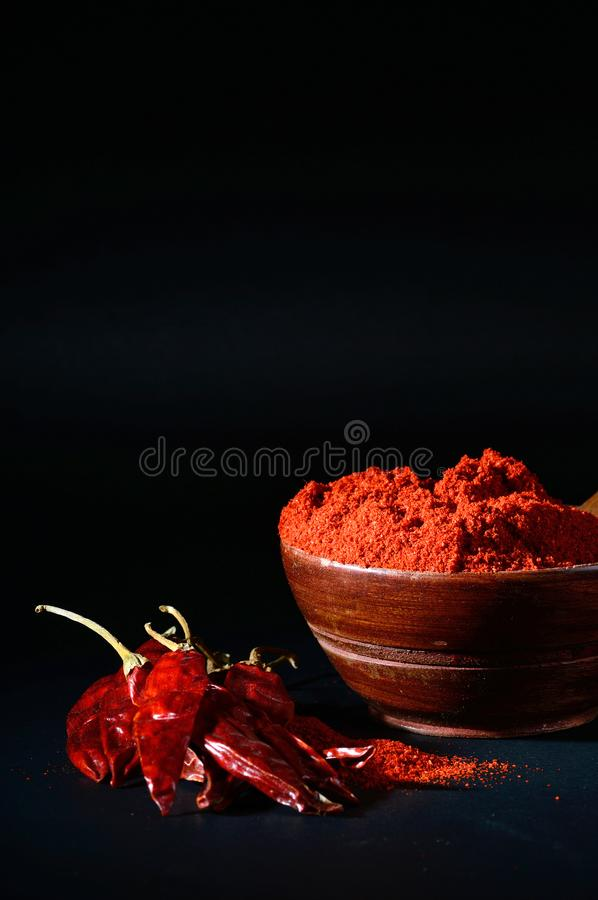 Chilly powder with red chilly in white plate. Chilly powder in wooden bowl with red chilly, dried chillies on black background stock image