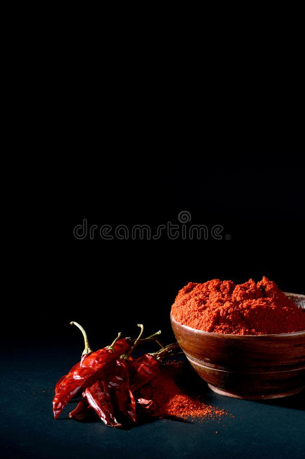 Chilly powder with red chilly in white plate. Chilly powder in wooden bowl with red chilly, dried chillies on black background stock photography