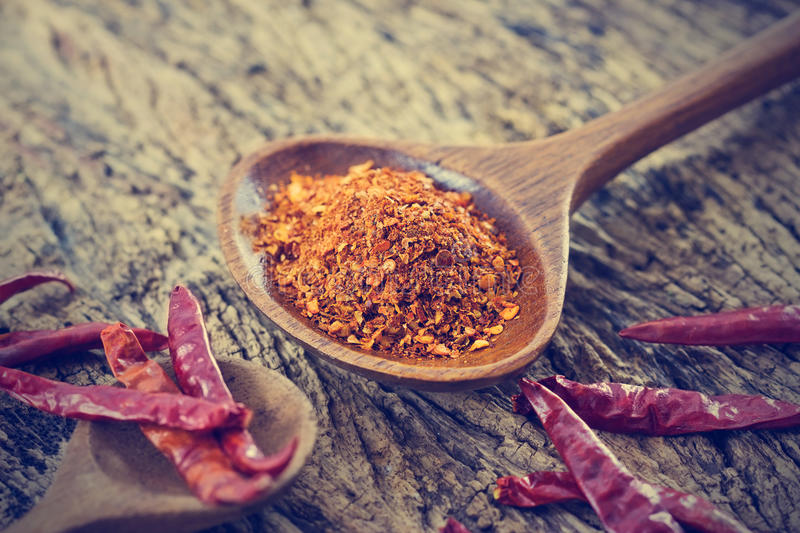 Chilly powder with red dried chilies in wooden spoon on old wooden royalty free stock photos