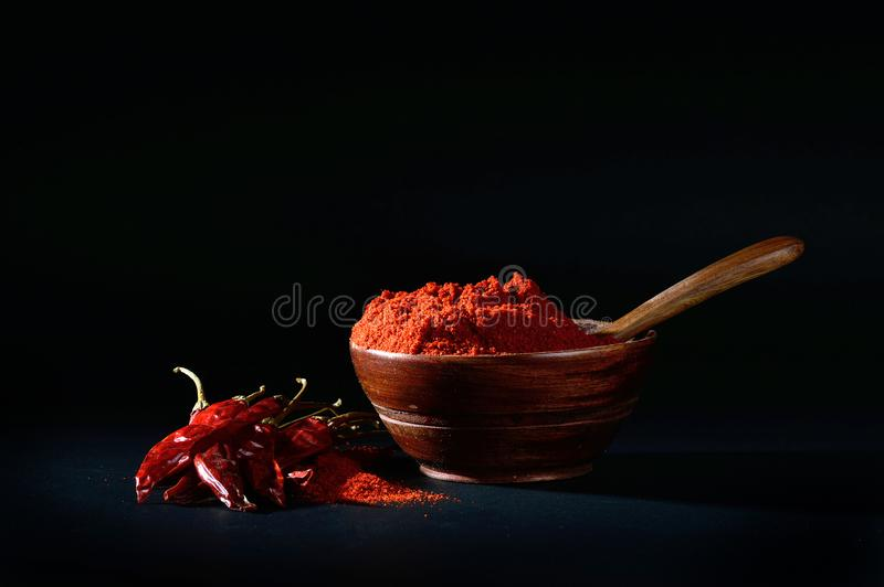 Chilly powder with red chilly in white plate. Chilly powder in wooden bowl with red chilly, dried chillies on black background royalty free stock image