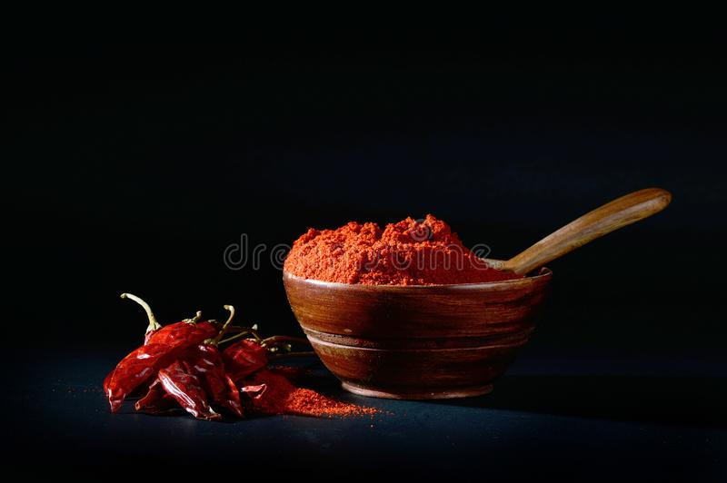 Chilly powder with red chilly in white plate. Chilly powder in wooden bowl with red chilly, dried chillies on black background royalty free stock images