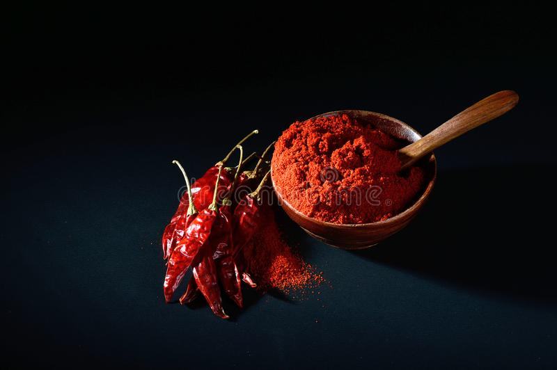 Chilly powder with red chilly in white plate. Chilly powder in wooden bowl with red chilly, dried chillies on black background royalty free stock photo