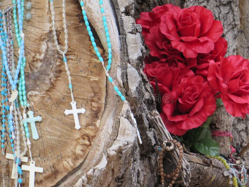 Chimayo, New Mexico. Flowers, rosaries and crosses in oak tree making religious shrine near church in Chimayo, New Mexico royalty free stock photography