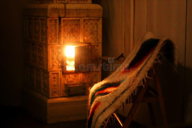 chimenea caliente y silla de madera con la manta nativa de lana, acogedora fotos de archivo libres de regalías