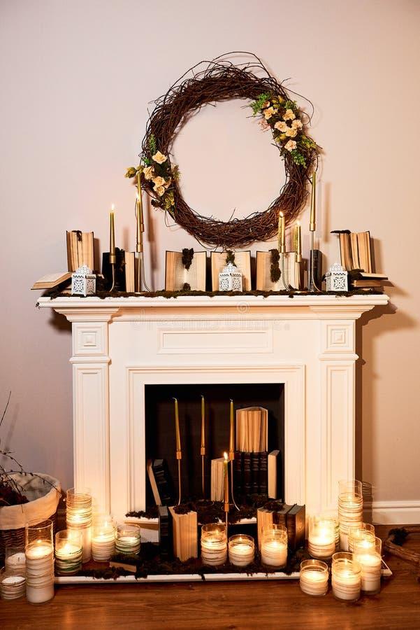 Chimenea con las velas, guirnalda del otoño en la pared fotos de archivo libres de regalías