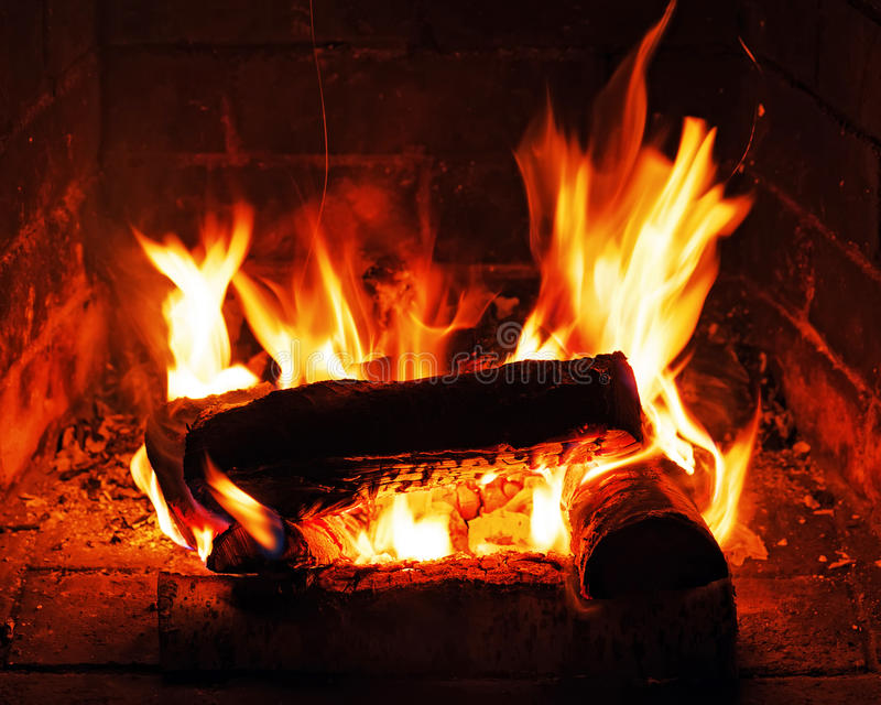 Chimenea con leña y la llama del abedul imagenes de archivo