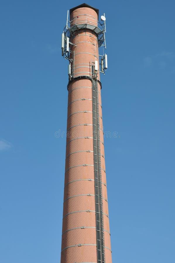 Chimenea del ladrillo con los sistemas celulares de la antena imagen de archivo