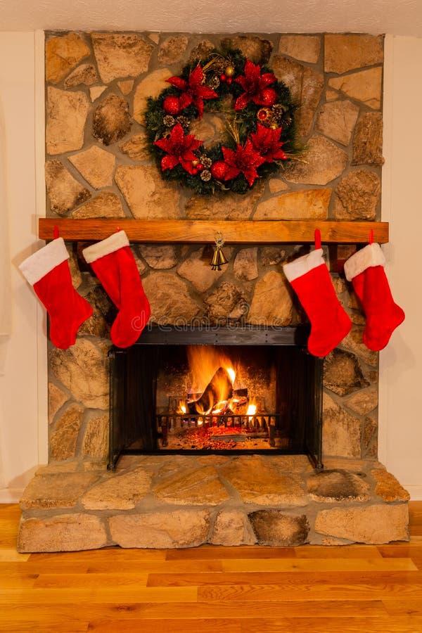 Chimenea diseñada para la Navidad con cuatro medias rojas, una campana y la guirnalda hermosa imagen de archivo libre de regalías