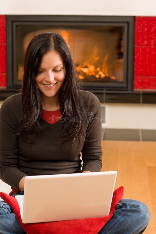 Chimenea feliz viva casera del ordenador del trabajo de la mujer foto de archivo