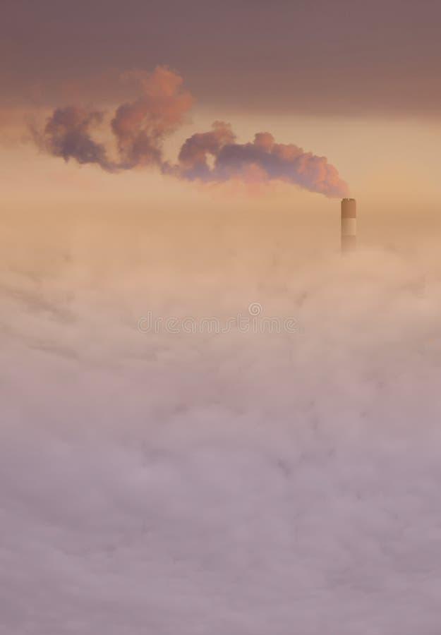 Chimenea grande de la central eléctrica con humo sobre la niebla con humo de la ciudad fotografía de archivo libre de regalías